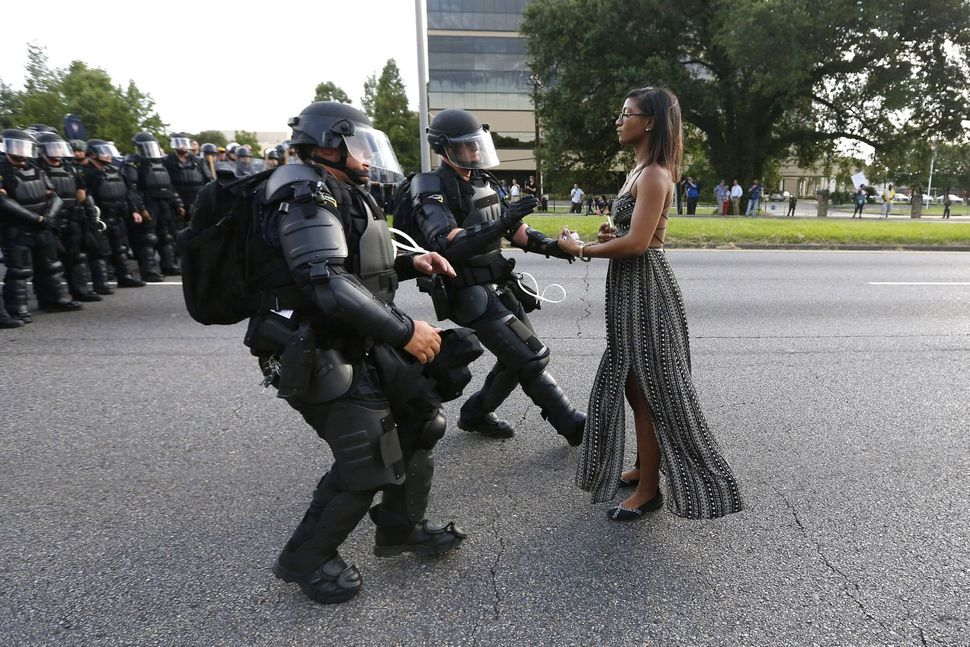 Lone activist Ieshia Evans stands her ground while offering her hands for arrest as she is charged by riot police during a pr