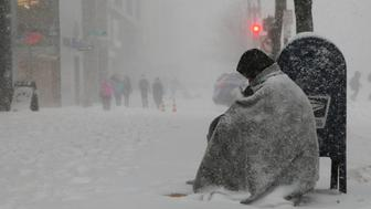 A homeless man asks for money outside a donut shop during white-out, blizzard-like conditions in a winter nor'easter snow storm in Boston, Massachusetts, U.S. February 9, 2017.   REUTERS/Brian Snyder