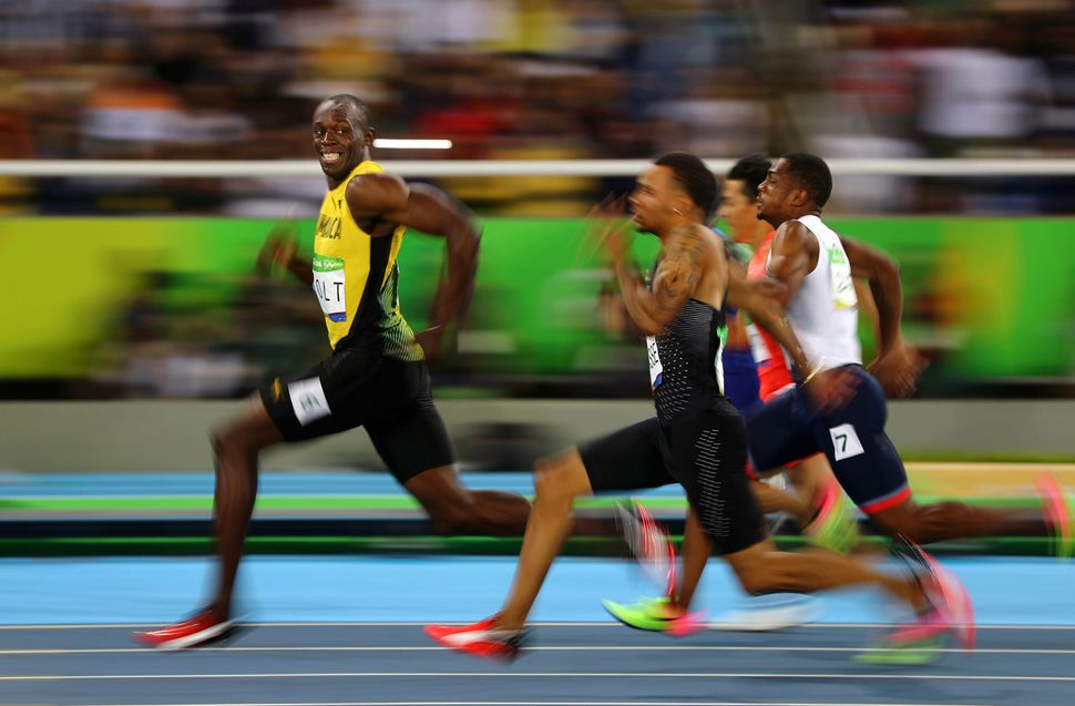 Usain Bolt of Jamaica smiles as he looks back at his competition, whilst winning the 100-meter semi-final sprint, at the 2016