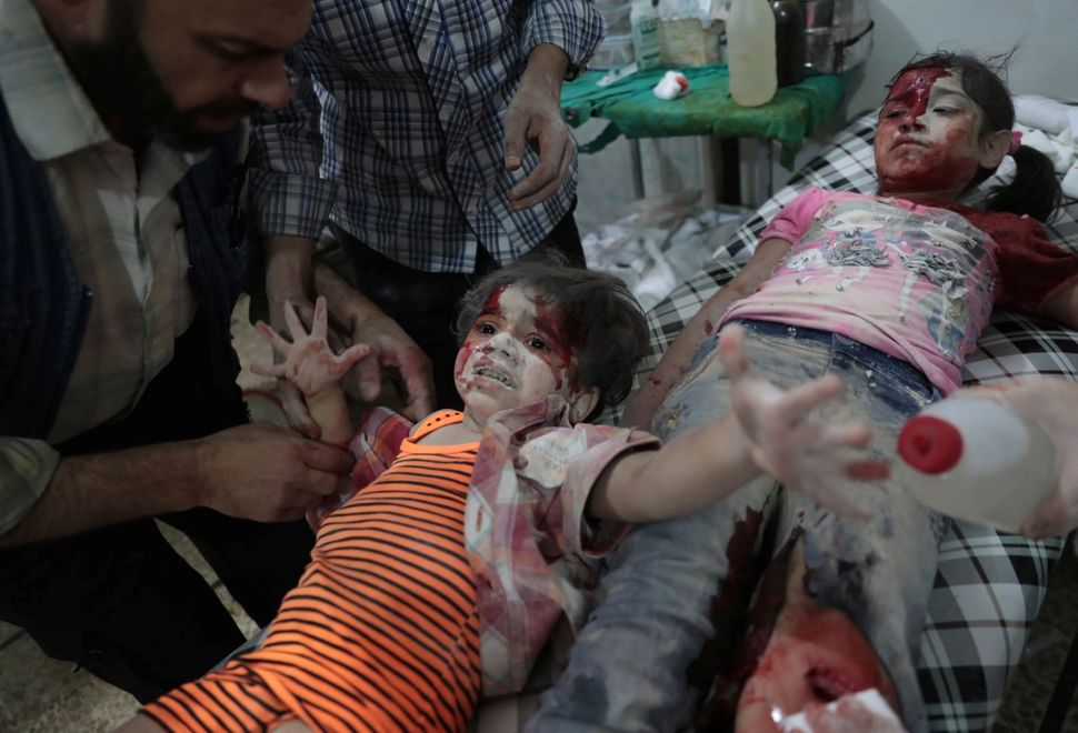 A Syrian girl cries out as a wounded child lies next to her at a makeshift hospital on Sept. 12. She had been injured in repo
