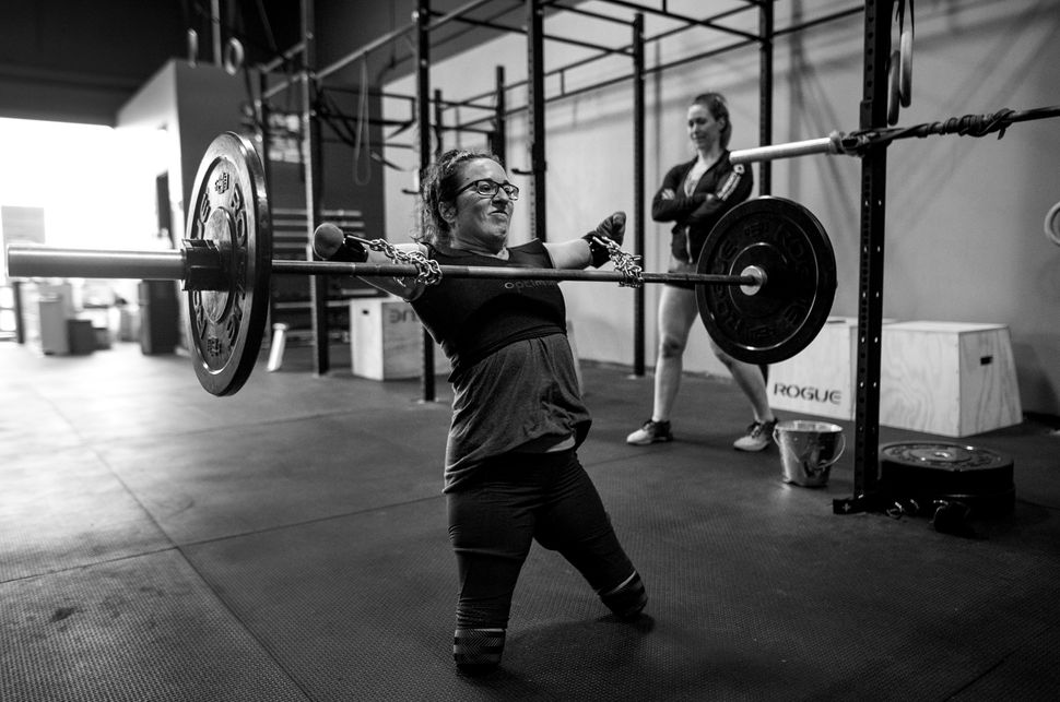 With the aid of chains purchased at the hardware store and deadlift straps, Lindsay performs cleans under the watchful eye of