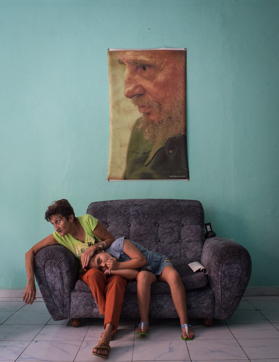 A woman strokes a girl's head as she rests on her lap whilst sitting on a sofa in a police station in Camaguey, Cuba, on Feb.
