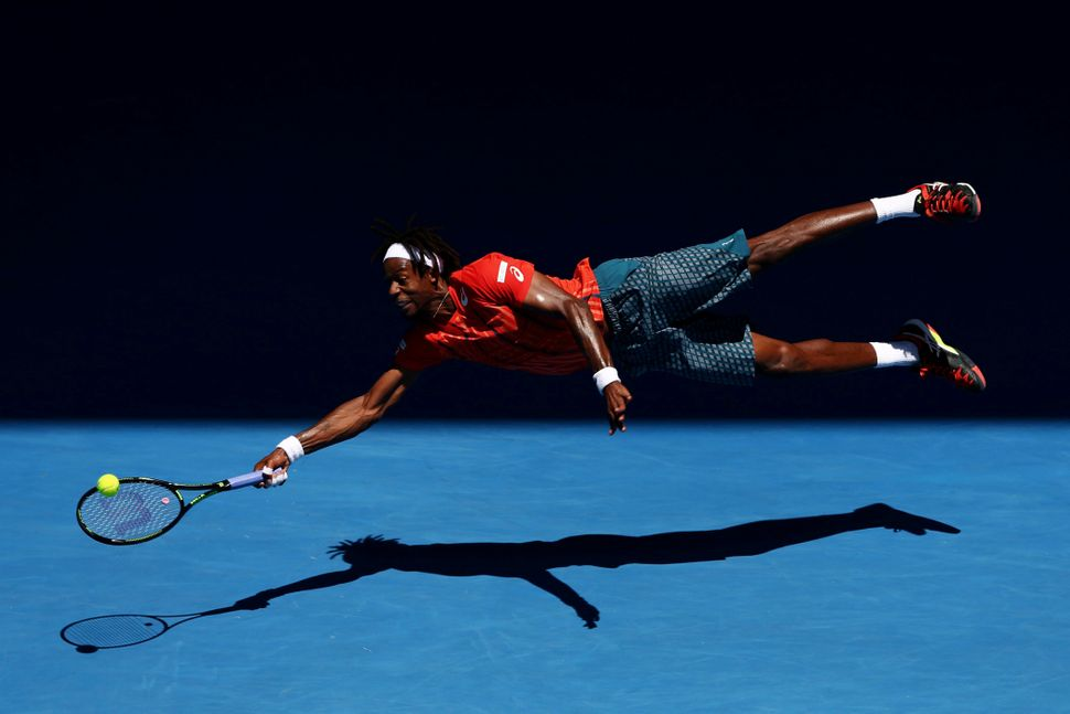 Gael Monfils of France dives for a forehand in his fourth-round match against Andrey Kuznetsov of Russia, during the 2016 Aus