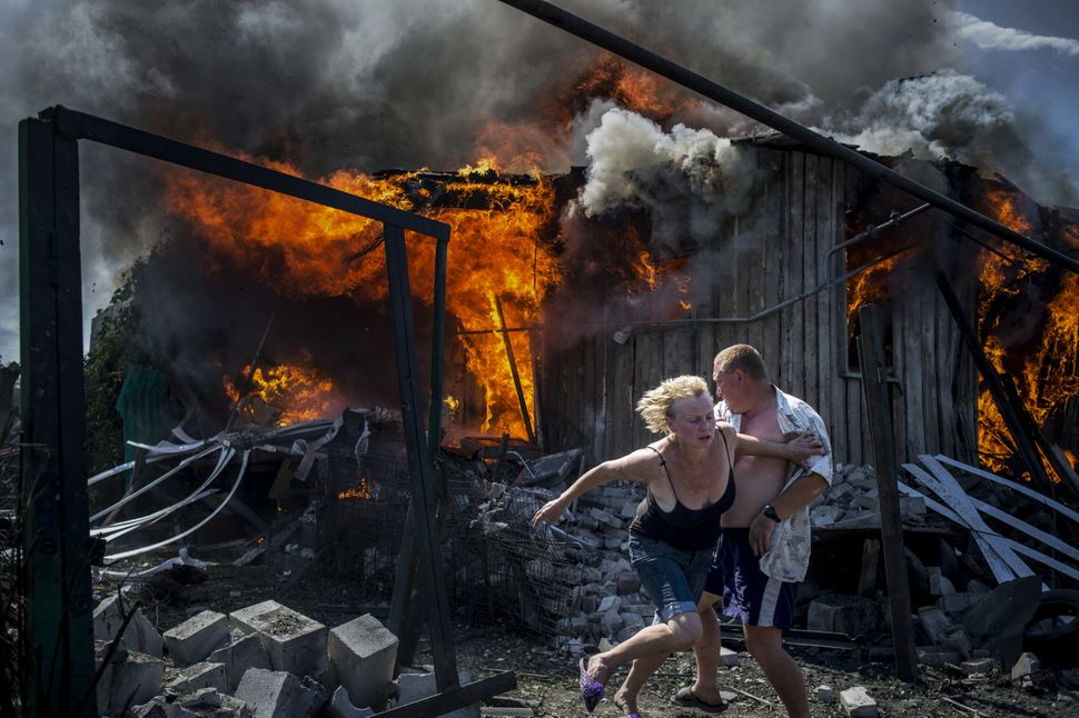 Civilians escape from a fire at a house destroyed by an air attack in Luhanskaya village, Ukraine.