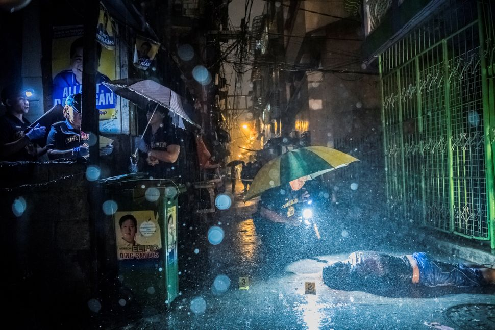 Heavy rain pours as police operatives investigate in an alley where Romeo Joel Torres Fontanilla, 37, was killed by two unide