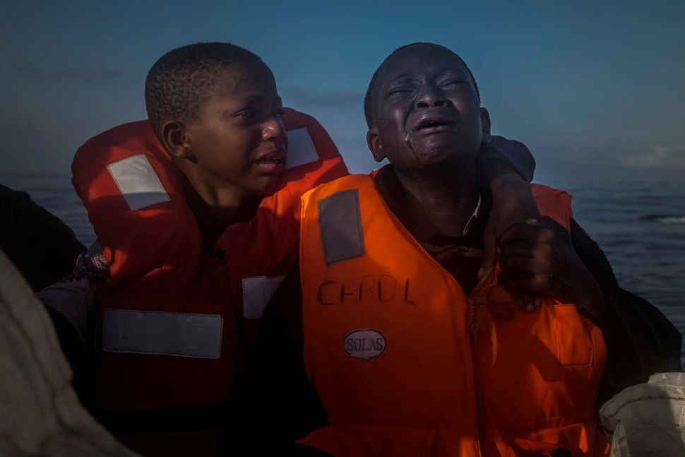 An 11-year-old girl from Nigeria (left), who said her mother died in Libya, cries next to her 10-year-old brother aboard a re