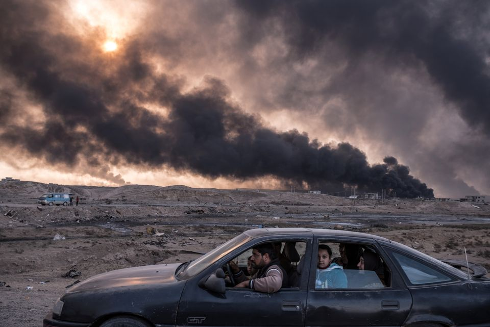 A family flees the fighting in Mosul, Iraq's second-largest city, as oil fields burned in Qayyara, Iraq,...