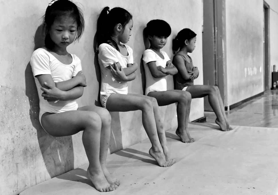 Four students of a gymnastics school in Xuzhou, China, do toe-pressure training for 30 minutes in the afternoon.
