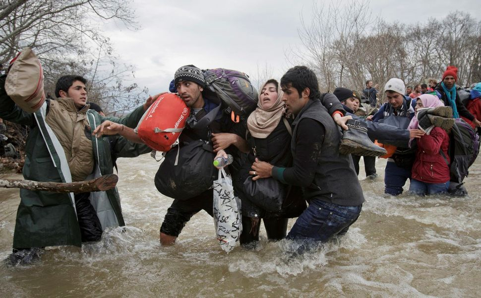 A woman is supported by two men while crossing a river, as refugees attempt to reach Macedonia on a route that would bypass t