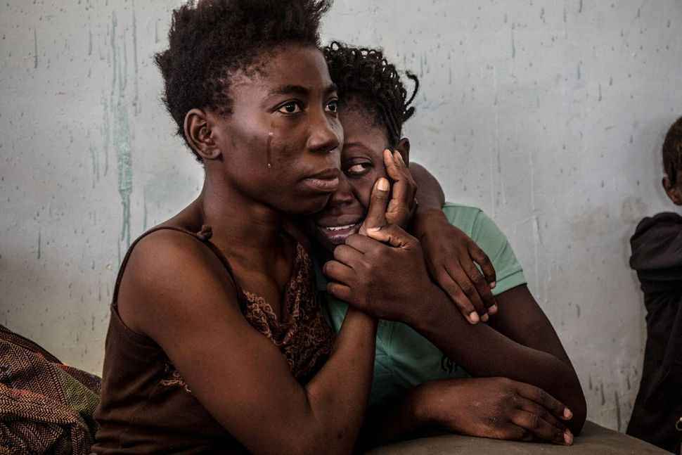 Two Nigerian refugees cry and embrace in a detention center for refugees in Surman, Libya Aug. 17, 2016. The detention center