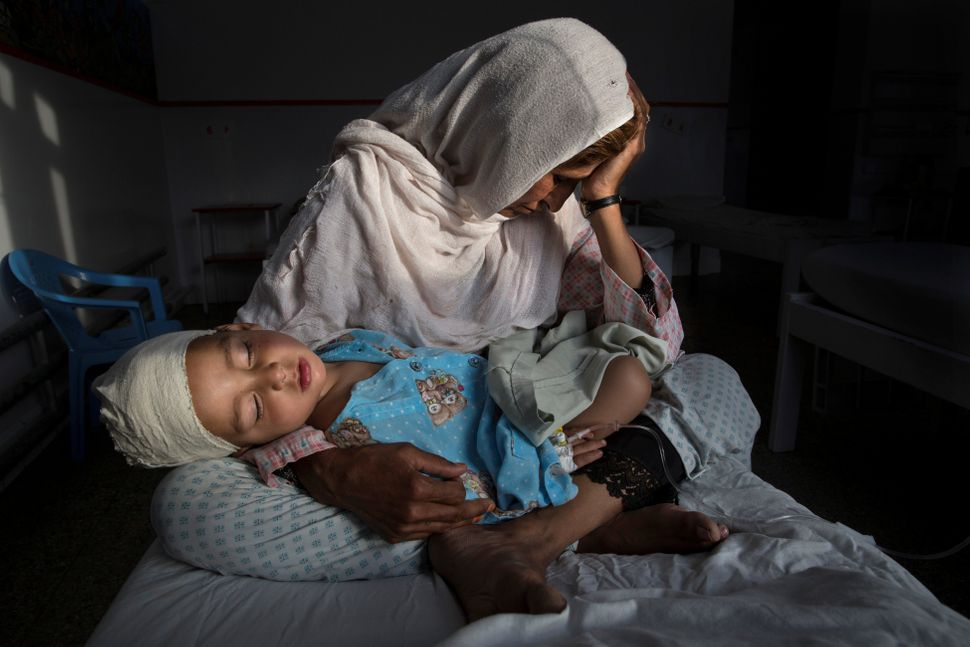 At the hospital, Najiba holds her 2-year-old nephew Shabir, who was injured from a bomb blast in Kabul on March 29, 2016. Afg