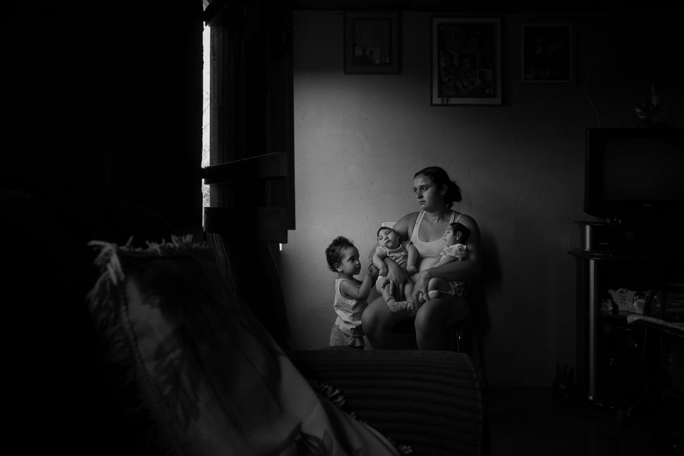 Marcela, 2, observes her sisters in her mother's lap at the family's home in the rural area of Areia. Twin sisters Heloisa (l