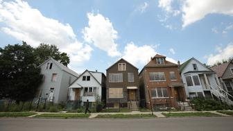 A man walks past five foreclosed homes in Chicago, July 21, 2010. (Photo by John Gress/Corbis via Getty Images)