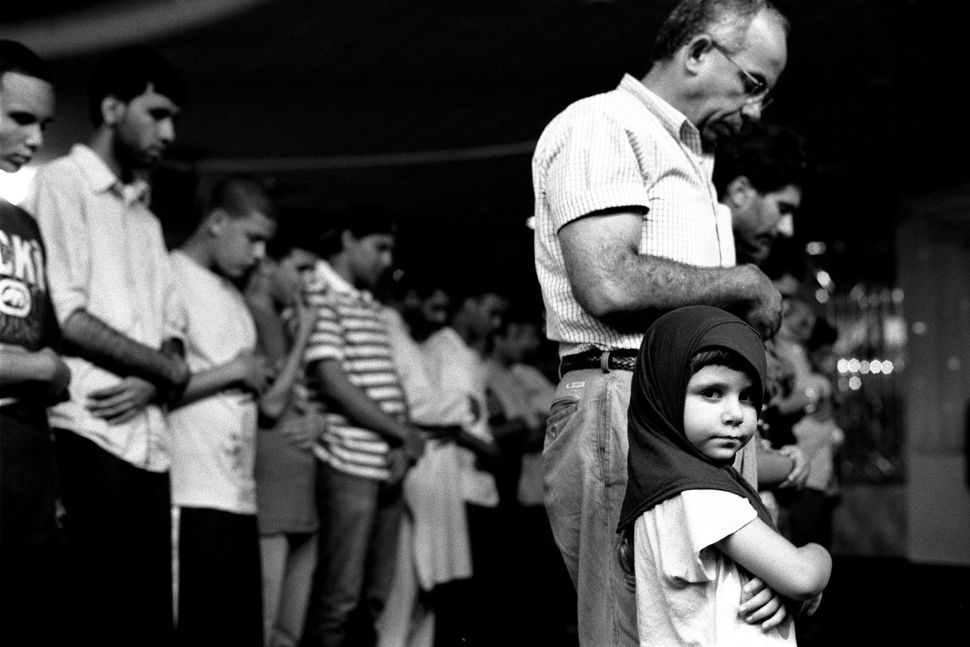 "Robert Gerhardt, ""Young Girl at Prayers with Her Father, Muslim American Society,"" Brooklyn, New York, 2010."