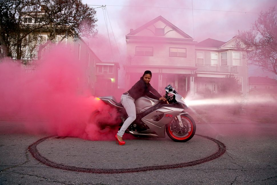 A member of Caramel Curves, an all-women motorcycle group, in a cloud of smoke.