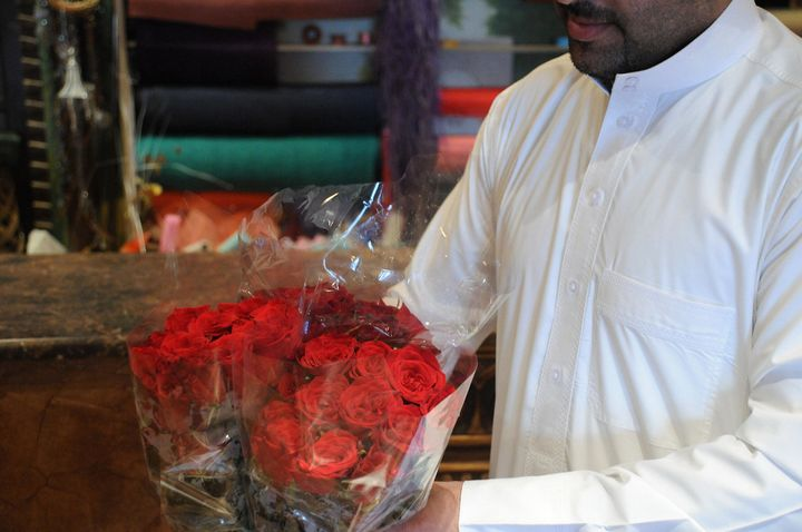 A Saudi man holds bouquets of red roses at a flower shop in the Saudi city of Dammam just before Valentine's Day, on Feb. 13,