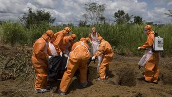 A burial team wearing protective clothes prepares an Ebola virus victim for interment, in Port Loko, Sierra Leone, September 27, 2014. To match Special Report HEALTH-WHO/LEADER REUTERS/Christopher Black/WHO/Handout via Reuters/File Photo ATTENTION EDITORS - THIS IMAGE HAS BEEN SUPPLIED BY A THIRD PARTY. FOR EDITORIAL USE ONLY.