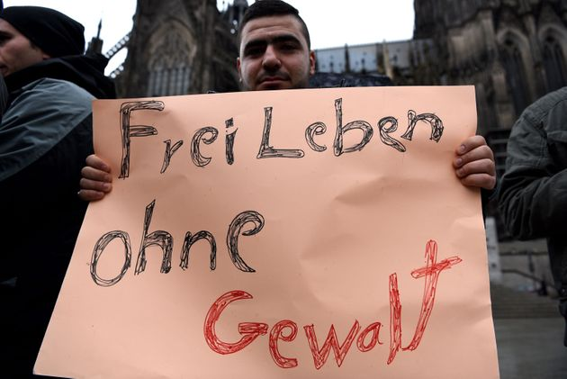 A refugee from Syria holds a sign reading 'Living feely without violence' as they demonstrate against...