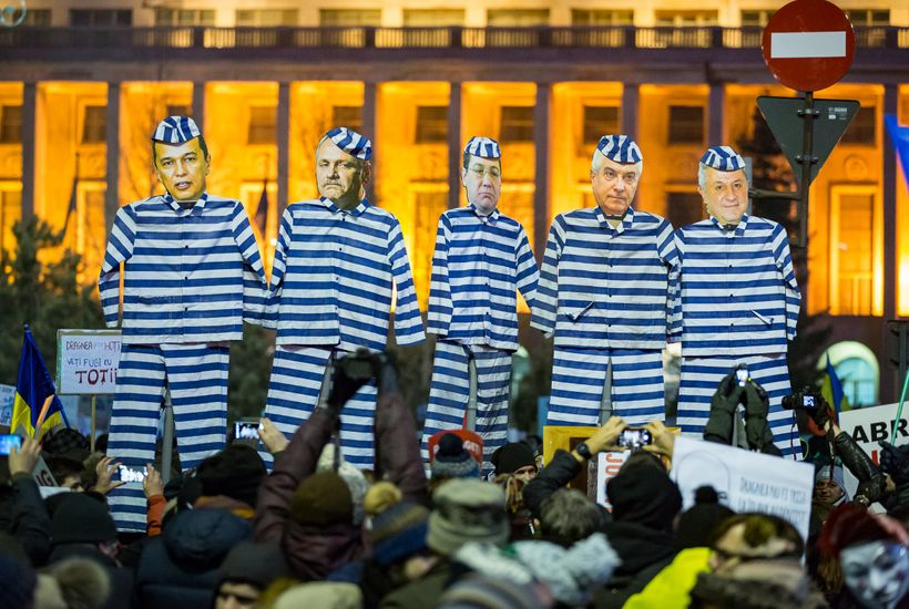 Protesters outside the government building in Bucharest hold up life-size cutouts of politicians in prison uniforms while cal
