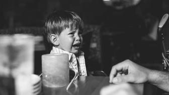 Black and white portrait of a little boy crying.