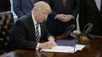 U.S. President Donald Trump signs executive orders inside the Oval Office of the White House in Washington, D.C., U.S., on Tuesday, Feb. 14, 2017. Michael Flynn's abrupt ouster from President Trump's top national security post prompted a flurry of Republicans calling for a deeper look into the administration's relations with Russia and Moscow's alleged interference in U.S. politics. Photographer: Olivier Douliery/Pool via Bloomberg