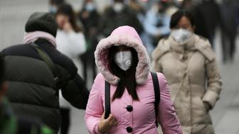 People wearing masks walk toward an office building during the smog after a red alert was issued for heavy air pollution in Beijing's central business district, China, December 21, 2016. REUTERS/Jason Lee