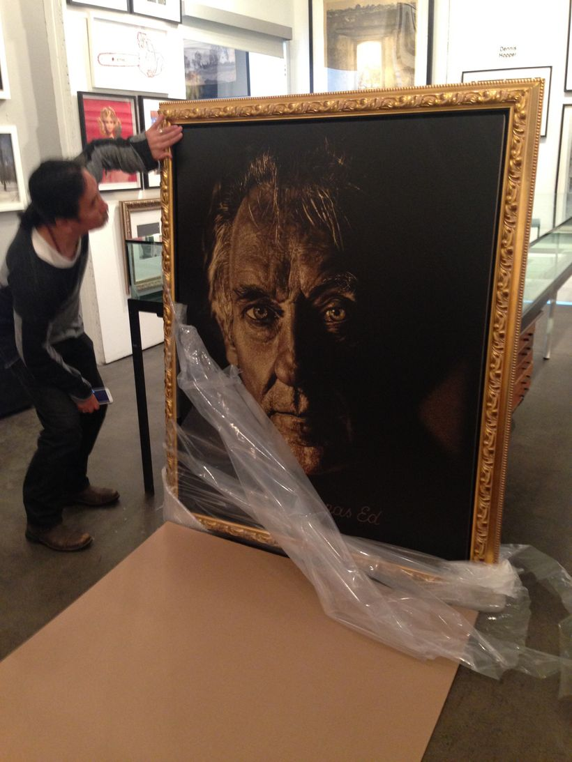 Artist Dennis Mukai unwrapping his work