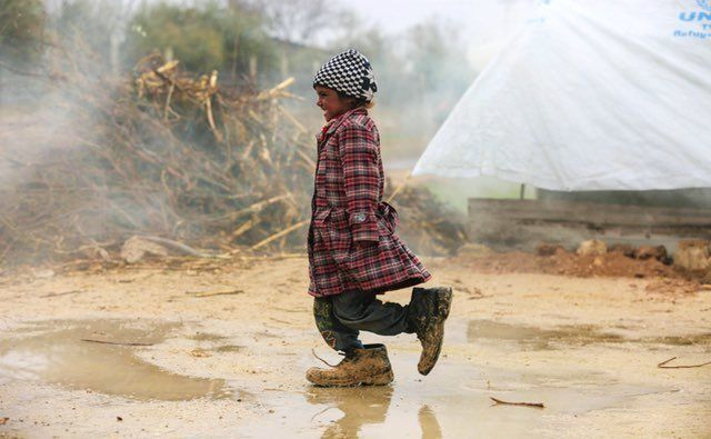 A displaced Syrian girl walks at a refugee camp in the eastern Ghouta region on the outskirts of the capital Damascus on Feb.