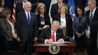 U.S. President Donald Trump, center, signs an executive order at the Department of Homeland Security (DHS) in Washington, D.C. U.S., on Wednesday, Jan. 25, 2017. Trump acted on two of the most fundamental -- and controversial -- elements of his presidential campaign, building a wall on the border with Mexico and greatly tightening restrictions on who can enter the U.S. Photographer: Chip Somodevilla/Pool via Bloomberg