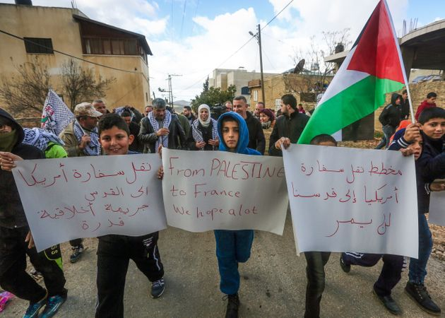 Palestinian children carry placards during a demonstration against proposed plans by President-elect...