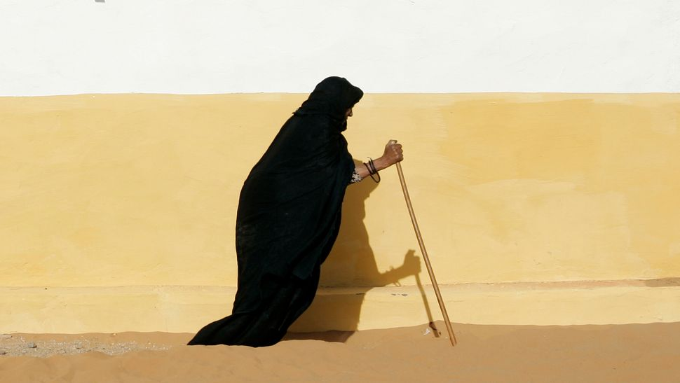 A Sahrawi woman walks with a stick at Dakhla's refugee camp, near Tindouf in southwestern Algeria, April 16, 2008.