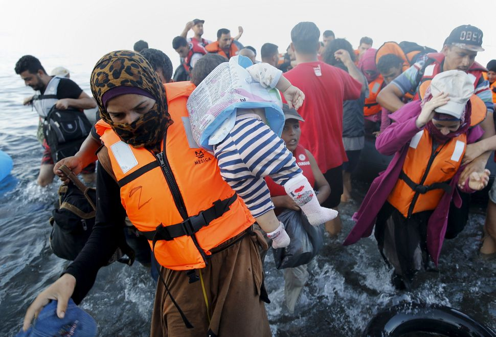 Syrian refugee mother carries her child off a dinghy after arriving at a beach on the Greek island of Lesbos after crossing a