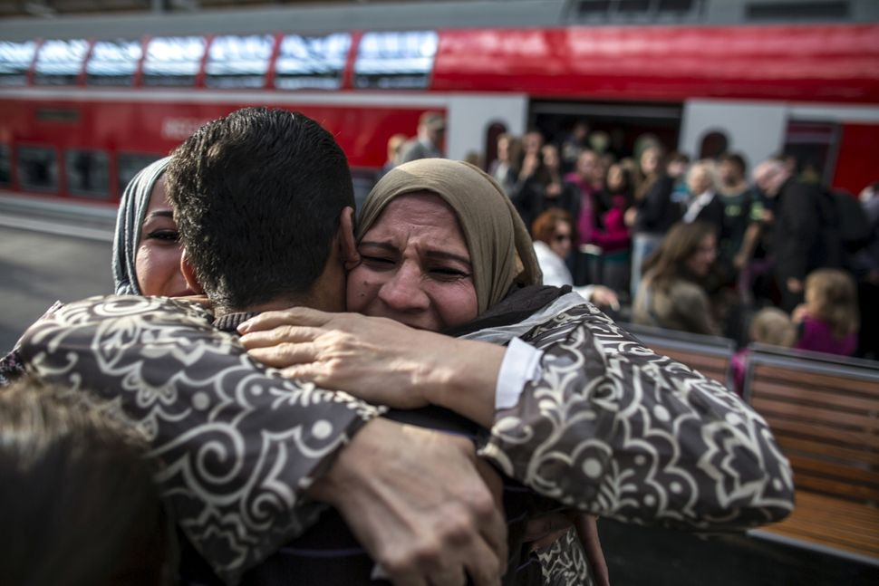 Houda, 48, hugs her son Ihab, 30, a Syrian migrant from Deir al-Zor, as he and his family arrive at the railway station in Lu