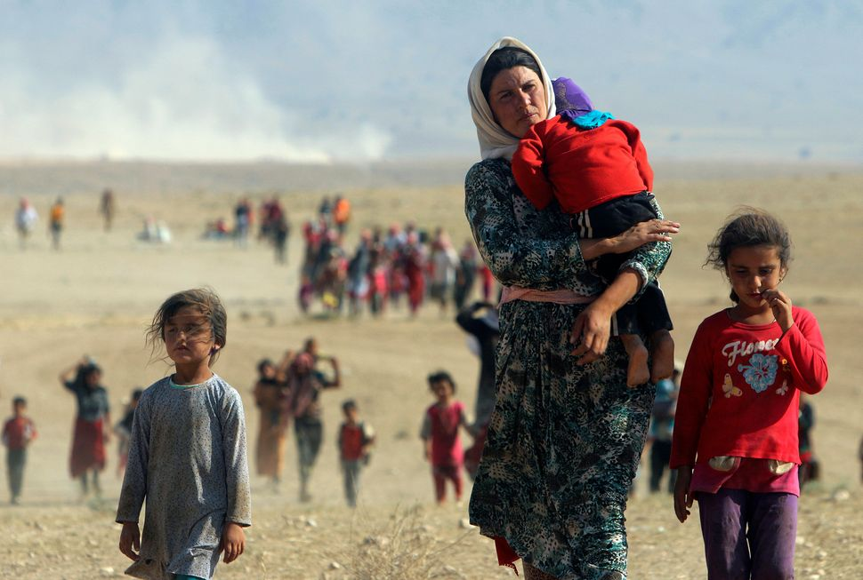 Displaced people from the minority Yazidi sect, fleeing violence from forces loyal to the Islamic State in Sinjar town, walk