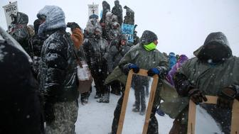 """Activists and veterans take part in a protest march outside the Oceti Sakowin camp where """"water protectors"""" continued to demonstrate against plans to pass the Dakota Access pipeline adjacent to the Standing Rock Indian Reservation, near Cannon Ball, North Dakota, U.S., December 5, 2016.  Picture taken December 5, 2016.   REUTERS/Stephen Yang"""