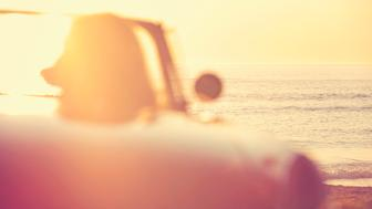 Woman driving a convertible at the beach. Shot is defocussed, with focus on the background.  It is sunset or sunrise. With the ocean in the background. Can be flipped for left hand drive car.