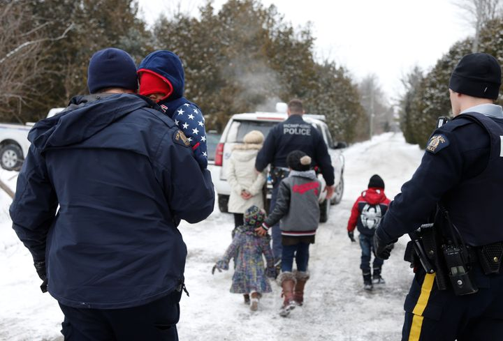 Royal Canadian Mounted Police officers take a Sudanese family into custody after they walked across the U.S.-Canada bord
