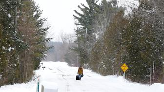 A man walks down Roxham Road in Champlain, New York, with his luggage toward the U.S.-Canada border in Hemmingford, Quebec, Canada February 13, 2017. Picture taken February 13, 2017. REUTERS/Christinne Muschi