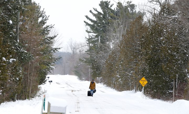 A man walks with his luggage down Roxham Road in Champlain, New York, toward the U.S.-Canada border in Hemmingford, Quebec, o