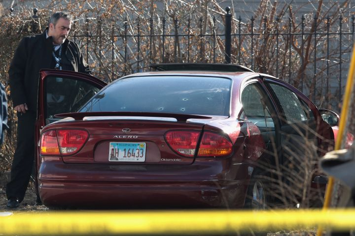 Police look over a car after a gunman opened fire Tuesday, killing a 2-year-old child and a man in his 20s and wounding