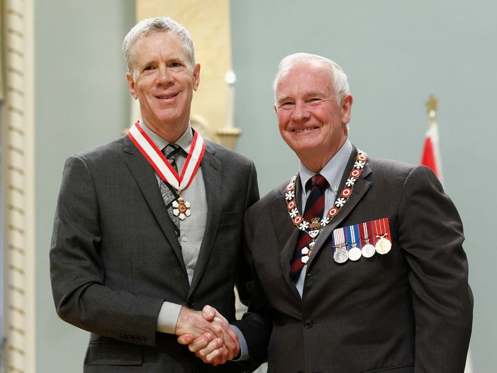 Stuart McLean, left, shakes hands with Governor General David Johnston after being awarded the rank of Officer in the Order o