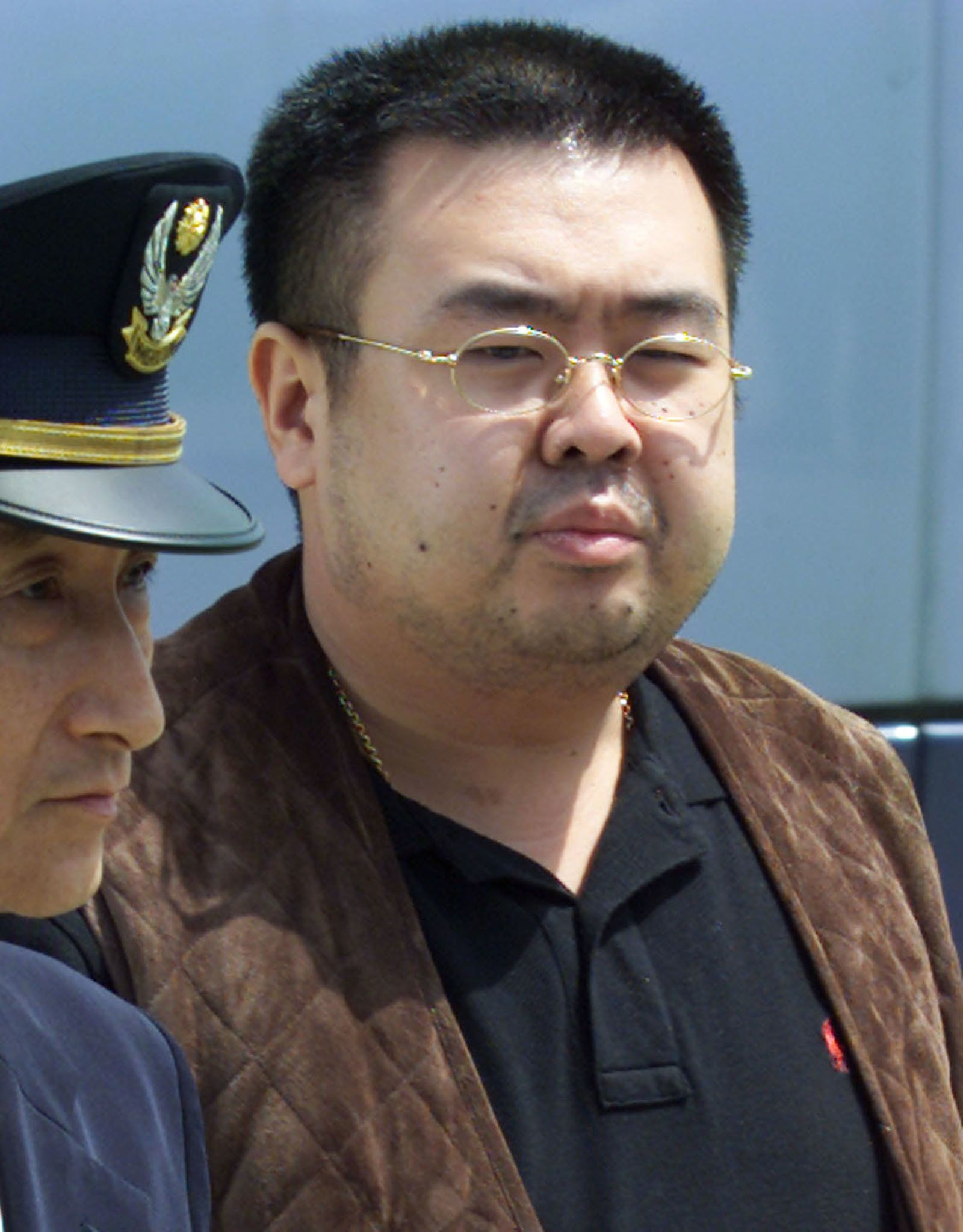 North Korean heir-apparent Kim Jong Nam is escorted by police as he boards a plane upon his deportation from Japan at Tokyo's Narita international airport May 4, 2001. Kim Jong Nam, eldest son of North Korean leader Kim Jong-il, the man entered Japan with a forged passport on Tuesday, but was deported to China on Friday.