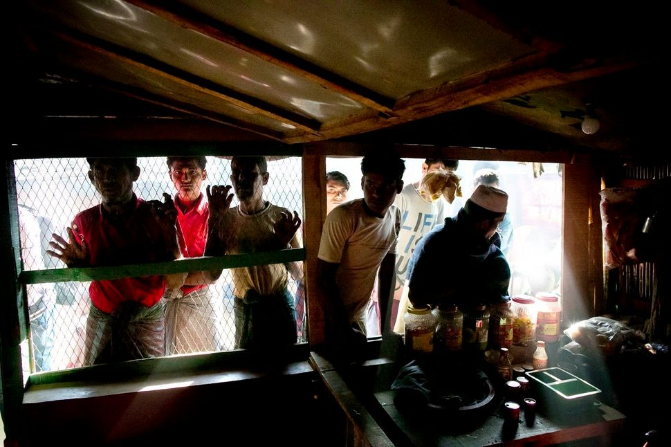 Rohingya refugees peer through the screen of a restaurant in Kutapalong.