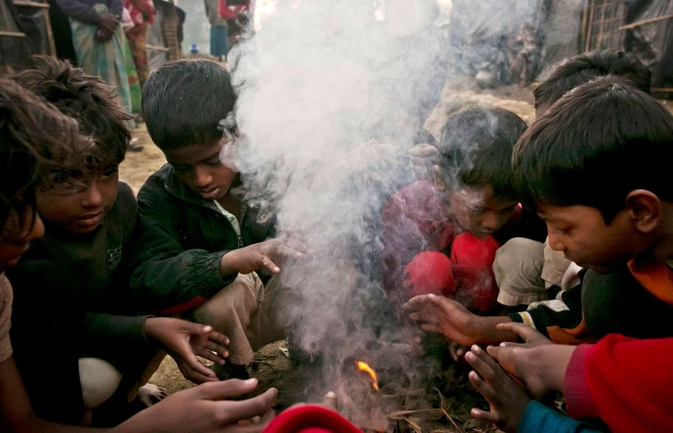 Newly arrived Rohingya children warm themselves by a fire in Kutapalong.