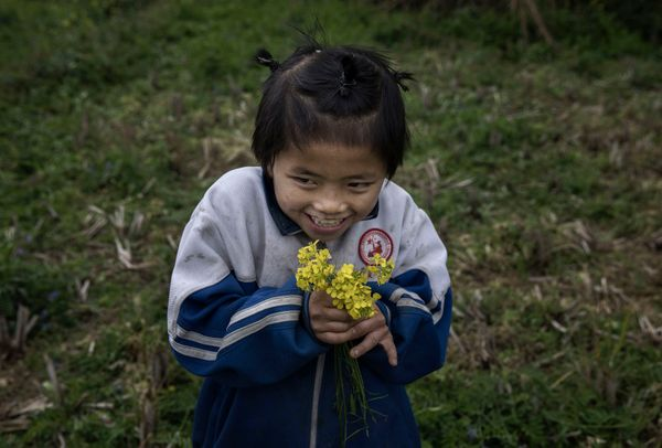 Luo Hongniu, 8, holds flowers she picked while doing chores.