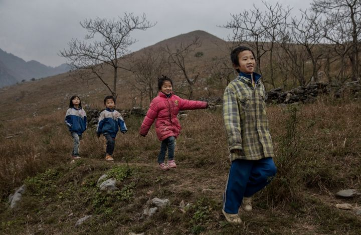 'Left behind' children from right to left, Luo Gan,10, Luo Hongniu, 8, Luo Lie, 5, and Luo Hongni, 11, walk together while do