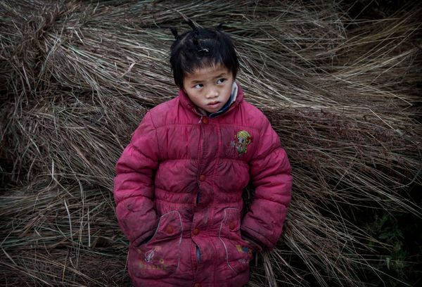 Luo Hongniu, 8, leans on hay bales while doing chores.