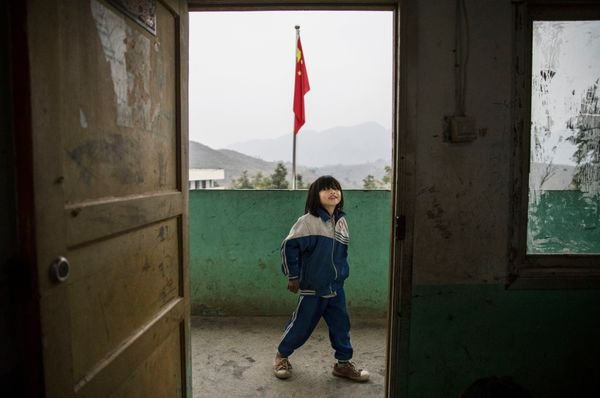 Luo Hongni, 11, waits outside her class at a local school.