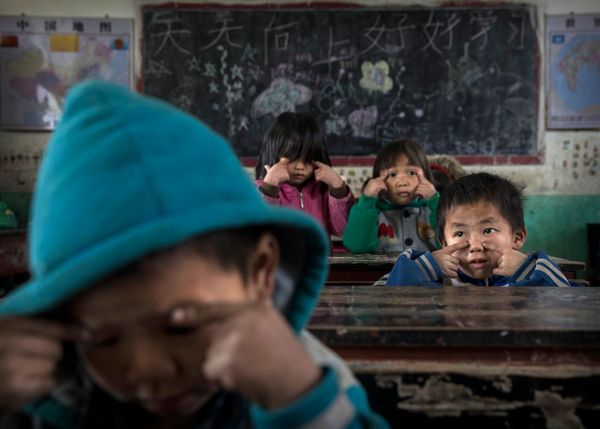 Luo Lie, 5, right, does eye exercises with classmates. Many children feel the absence of interaction with their mother and/or