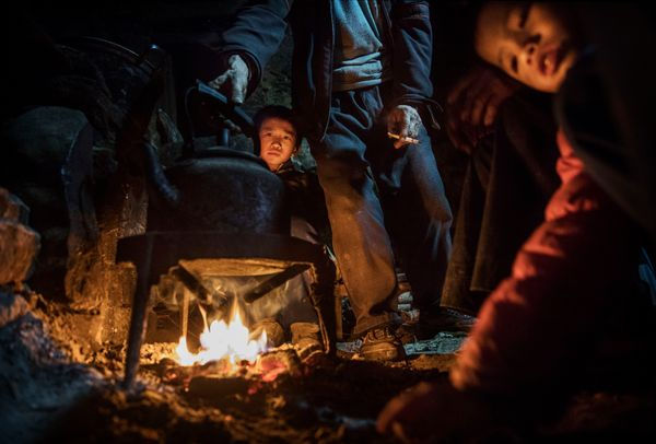 Luo Gan, 10, stays warm by a fire at the family house.